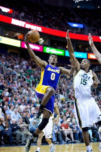 Apr 14, 2014; Salt Lake City, UT, USA; Los Angeles Lakers forward Nick Young (0) goes to the basket in front of Utah Jazz center Derrick Favors (15) during the first half at EnergySolutions Arena. Mandatory Credit: Russ Isabella-USA TODAY Sports