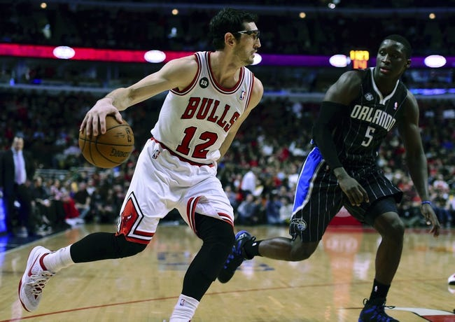 Apr 14, 2014; Chicago, IL, USA; Chicago Bulls guard Kirk Hinrich (12) dribbles the ball against Orlando Magic guard Victor Oladipo (5) during the second half at the United Center. Chicago defeats Orlando 108-95. Mandatory Credit: Mike DiNovo-USA TODAY Sports