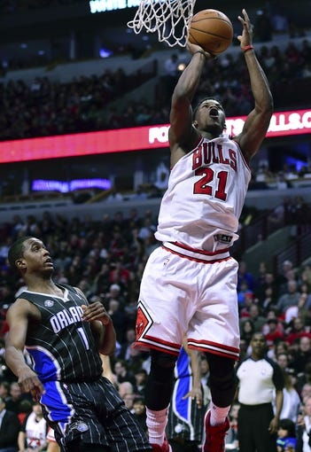 Apr 14, 2014; Chicago, IL, USA; Chicago Bulls guard Jimmy Butler (21) shoots the ball against Orlando Magic guard Doron Lamb (1) during the second half at the United Center. Chicago defeats Orlando 108-95. Mandatory Credit: Mike DiNovo-USA TODAY Sports