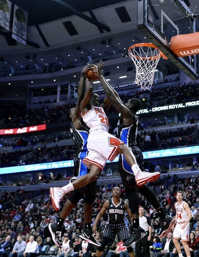 Apr 14, 2014; Chicago, IL, USA; Chicago Bulls guard Tony Snell (20) is defended by Orlando Magic center Dewayne Dedmon (3) and forward Andrew Nicholson (44) during the second half at the United Center. Chicago defeats Orlando 108-95. Mandatory Credit: Mike DiNovo-USA TODAY Sports