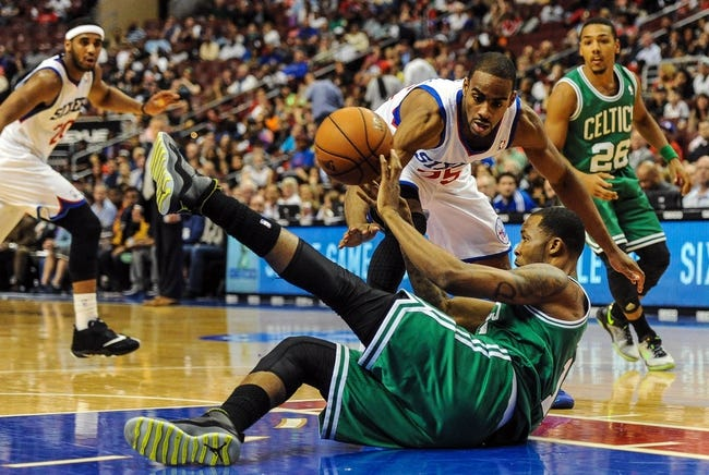 Apr 14, 2014; Philadelphia, PA, USA; Philadelphia 76ers guard Elliot Williams (25) and Boston Celtics forward Chris Johnson (12) battle for a loose ball in the third quarter of the game at Wells Fargo Center. The Philadelphia 76ers won 113-108. Mandatory Credit: John Geliebter-USA TODAY Sports