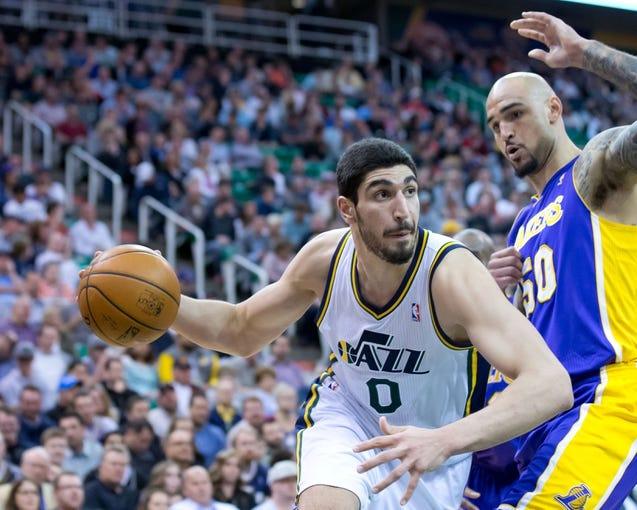 Apr 14, 2014; Salt Lake City, UT, USA; Utah Jazz center Enes Kanter (0) dribbles around Los Angeles Lakers center Robert Sacre (50) during the second half at EnergySolutions Arena. The Lakers won 119-104. Mandatory Credit: Russ Isabella-USA TODAY Sports