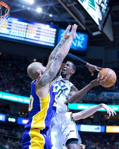 Apr 14, 2014; Salt Lake City, UT, USA; Utah Jazz forward Jeremy Evans (40) loses control of the ball as he goes up for a shot against Los Angeles Lakers center Robert Sacre (50) during the second half at EnergySolutions Arena. The Lakers won 119-104. Mandatory Credit: Russ Isabella-USA TODAY Sports