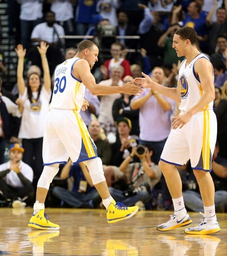 Apr 14, 2014; Oakland, CA, USA; Golden State Warriors guard Stephen Curry (30) celebrates with guard Klay Thompson (11) after a basket against the Minnesota Timberwolves during the fourth quarter at Oracle Arena. The Golden State Warriors defeated the Minnesota Timberwolves 130-120. Mandatory Credit: Kelley L Cox-USA TODAY Sports