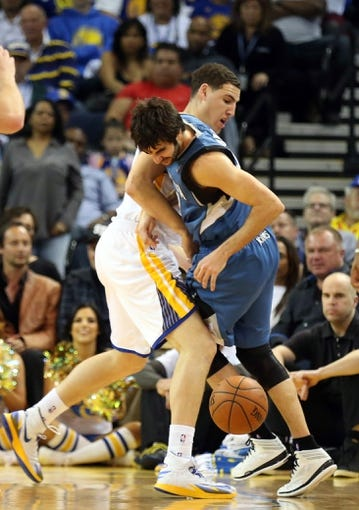 Apr 14, 2014; Oakland, CA, USA; Golden State Warriors guard Klay Thompson (11) fouls Minnesota Timberwolves guard Ricky Rubio (9) during the third quarter at Oracle Arena. The Golden State Warriors defeated the Minnesota Timberwolves 130-120. Mandatory Credit: Kelley L Cox-USA TODAY Sports