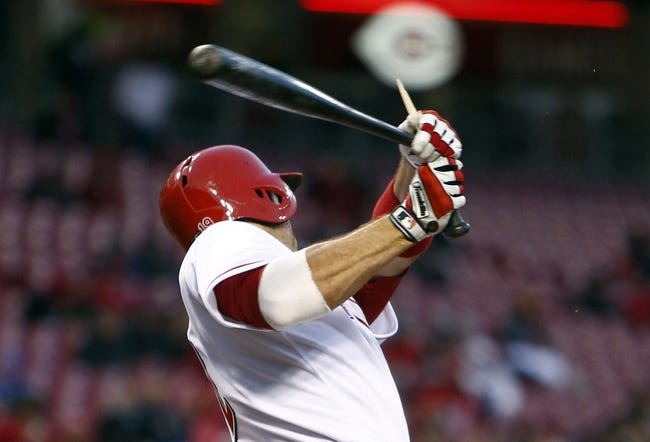 Apr 15, 2014; Cincinnati, OH, USA; Cincinnati Reds first baseman Joey Votto hits a broken-bat RBI single off Pittsburgh Pirates starting pitcher Gerrit Cole during the third inning at Great American Ball Park. Mandatory Credit: David Kohl-USA TODAY Sports