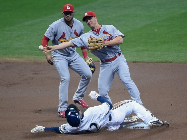 Apr 15, 2014; Milwaukee, WI, USA;  St. Louis Cardinals second baseman Mark Ellis (right) completes a double play after forcing out Milwaukee Brewers center fielder Carlos Gomez (center) as shortstop Jhonny Peralta watches in the first inning at Miller Park. Mandatory Credit: Benny Sieu-USA TODAY Sports