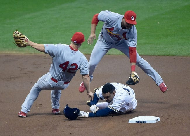 Apr 15, 2014; Milwaukee, WI, USA;  Milwaukee Brewers center fielder Carlos Gomez (center) upends St. Louis Cardinals second baseman Mark Ellis (left) and shortstop Jhonny Peralta (right) after he was forced out at 2nd base on a double play in the first inning at Miller Park. Mandatory Credit: Benny Sieu-USA TODAY Sports