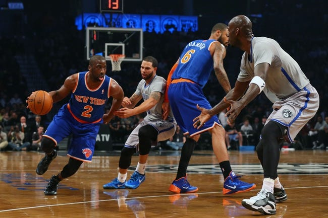Apr 15, 2014; Brooklyn, NY, USA;  New York Knicks guard Raymond Felton (2) drives past Brooklyn Nets guard Deron Williams (8) and center Kevin Garnett (2) during the first quarter at Barclays Center. Mandatory Credit: Anthony Gruppuso-USA TODAY Sports