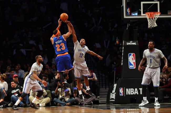 Apr 15, 2014; Brooklyn, NY, USA;  New York Knicks guard Toure' Murry (23) shoots over Brooklyn Nets guard Marquis Teague (12) during the fourth quarter at Barclays Center. New York Knicks won 109-98.  Mandatory Credit: Anthony Gruppuso-USA TODAY Sports