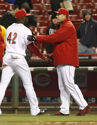 Apr 15, 2014; Cincinnati, OH, USA; Cincinnati Reds manager Bryan Price, right, congratulates left fielder Roger Bernadina, left, after the Reds defeated the Pittsburgh Pirates 7-5 at Great American Ball Park. Mandatory Credit: David Kohl-USA TODAY Sports