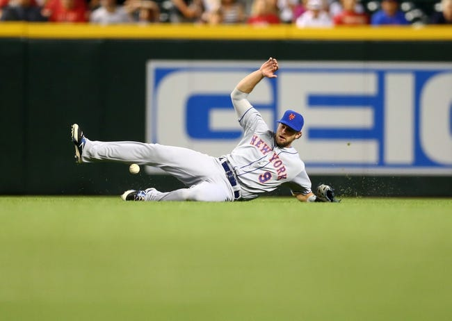 Apr 16, 2014; Phoenix, AZ, USA; New York Mets outfielder Kirk Nieuwenhuis is unable to make a sliding catch in the sixth inning against the Arizona Diamondbacks at Chase Field. Mandatory Credit: Mark J. Rebilas-USA TODAY Sports
