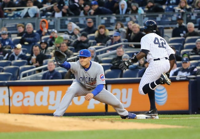 Apr 16, 2014; Bronx, NY, USA;  New York Yankees designated hitter Alfonso Soriano (12) safe at first as Chicago Cubs first baseman Anthony Rizzo (44) waits for the ball during the first inning at Yankee Stadium. Mandatory Credit: Anthony Gruppuso-USA TODAY Sports