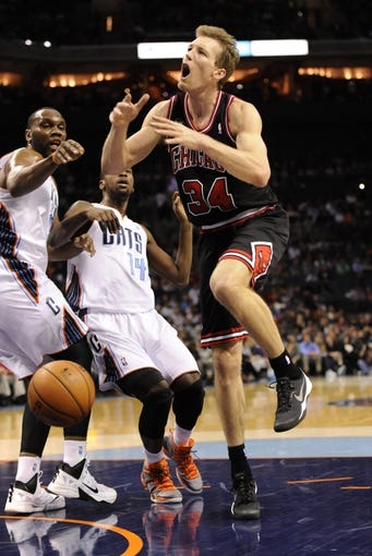 Apr 16, 2014; Charlotte, NC, USA; Chicago Bulls forward Mike Dunleavy (34) gets the ball stripped by Charlotte Bobcats center Al Jefferson (25) and forward Michael Kidd-Gilchrist (14) during the first half of the game at Time Warner Cable Arena. Mandatory Credit: Sam Sharpe-USA TODAY Sports