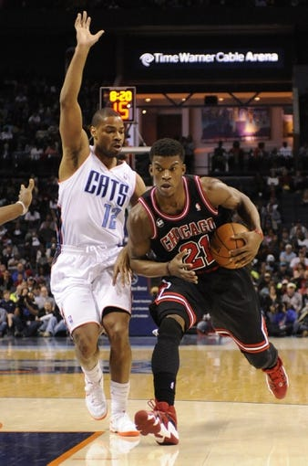 Apr 16, 2014; Charlotte, NC, USA; Chicago Bulls guard forward Jimmy Butler (21) drives into the Charlotte Bobcats defense of guard Gary Neal (12) and forward center Bismack Biyombo (0) during the first half of the game at Time Warner Cable Arena. Mandatory Credit: Sam Sharpe-USA TODAY Sports