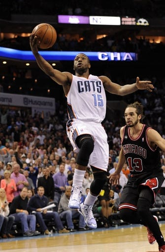 Apr 16, 2014; Charlotte, NC, USA; Charlotte Bobcats guard Kemba Walker (15) drives to the basket past Chicago Bulls center Joakim Noah (13) during the second half of the game at Time Warner Cable Arena. Bobcats win in overtime 91-86. Mandatory Credit: Sam Sharpe-USA TODAY Sports