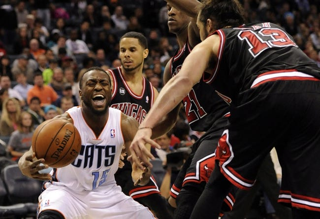 Apr 16, 2014; Charlotte, NC, USA; Charlotte Bobcats guard Kemba Walker (15) looks to pass as he is defended by Chicago Bulls guard D.J. Augustin (13) guard forward Jimmy Butler (21) and center Joakim Noah (13) during the second half of the game at Time Warner Cable Arena. Bobcats win in overtime 91-86. Mandatory Credit: Sam Sharpe-USA TODAY Sports