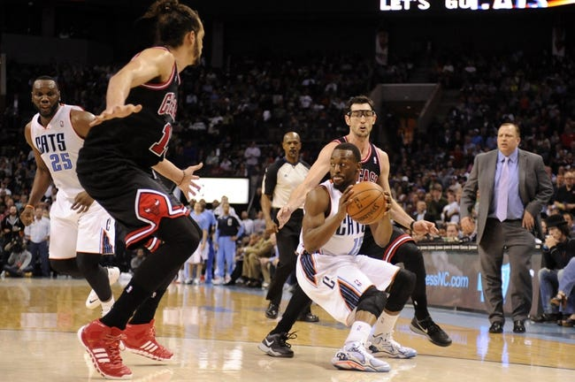 Apr 16, 2014; Charlotte, NC, USA; Charlotte Bobcats guard Kemba Walker (15) looks to pass as he is defended by Chicago Bulls center Joakim Noah (13) and guard Kirk Hinrich (12) during the second half of the game at Time Warner Cable Arena. Bobcats win in overtime 91-86. Mandatory Credit: Sam Sharpe-USA TODAY Sports