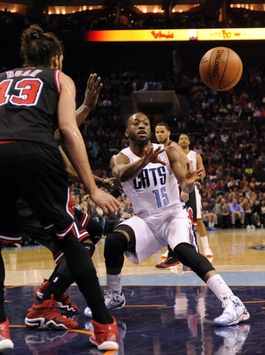 Apr 16, 2014; Charlotte, NC, USA; Charlotte Bobcats guard Kemba Walker (15) passes the ball as he is defended by Chicago Bulls center Joakim Noah (13) during the second half of the game at Time Warner Cable Arena. Bobcats win in overtime 91-86. Mandatory Credit: Sam Sharpe-USA TODAY Sports