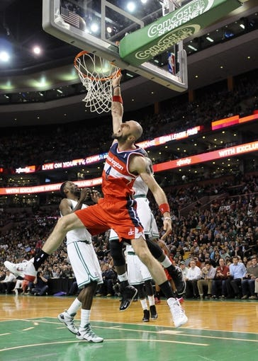 Apr 16, 2014; Boston, MA, USA; Washington Wizards center Marcin Gortat (4) hangs onto the rim during the second half against the Boston Celtics at TD Garden. Mandatory Credit: Bob DeChiara-USA TODAY Sports