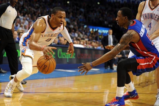 Apr 16, 2014; Oklahoma City, OK, USA;  Oklahoma City Thunder guard Russell Westbrook (0) handles the ball against Detroit Pistons guard Kentavious Caldwell-Pope (5) during the fourth quarter at Chesapeake Energy Arena. Mandatory Credit: Mark D. Smith-USA TODAY Sports