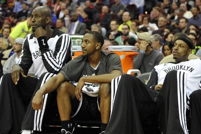 Apr 12, 2014; Cleveland, OH, USA; Brooklyn Nets center Kevin Garnett (left), guard Marquis Teague (center) and forward Paul Pierce (34) sit on the bench in the first quarter against the Cleveland Cavaliers at Quicken Loans Arena. Mandatory Credit: David Richard-USA TODAY Sports
