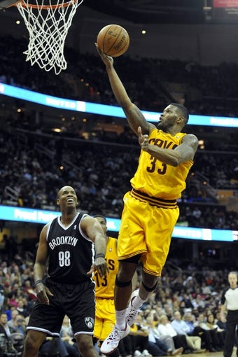 Apr 12, 2014; Cleveland, OH, USA; Cleveland Cavaliers forward Alonzo Gee (33) shoots against Brooklyn Nets center Jason Collins (98) in the third quarter at Quicken Loans Arena. Mandatory Credit: David Richard-USA TODAY Sports
