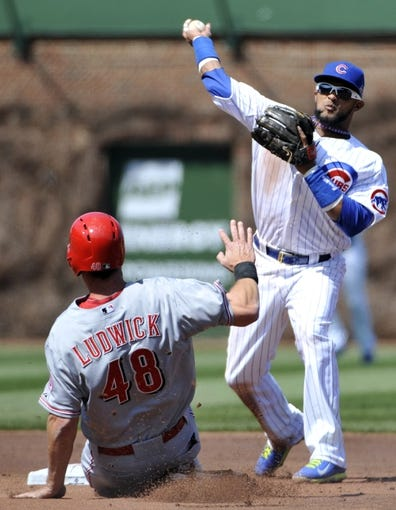 Apr 18, 2014; Chicago, IL, USA;  Chicago Cubs second baseman Emilio Bonifacio (64) forces out Cincinnati Reds left fielder Ryan Ludwick (48) during the second inning at Wrigley Field. Mandatory Credit: David Banks-USA TODAY Sports