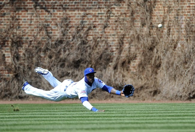 Apr 18, 2014; Chicago, IL, USA;  Chicago Cubs left fielder Junior Lake (21) tries to make a catch on a RBI double by Cincinnati Reds center fielder Billy Hamilton (not pictured) during the sixth inning at Wrigley Field. Mandatory Credit: David Banks-USA TODAY Sports