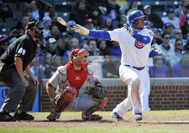 Apr 18, 2014; Chicago, IL, USA; Chicago Cubs third baseman Luis Valbuena (24) hits an RBI single against the Cincinnati Reds during the seventh inning at Wrigley Field. Mandatory Credit: David Banks-USA TODAY Sports
