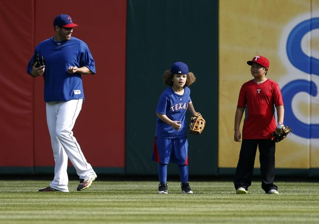 Apr 18, 2014; Arlington, TX, USA; Texas Rangers pitcher Colby Lewis smiles at Jaden Fielder (left), the son of Prince Fielder (not pictured) and Alan Choo, the son of Shin-Soo Choo (not pictured) during batting practice before the baseball game between the Texas Rangers and the Chicago White Sox at Rangers Ballpark in Arlington. Mandatory Credit: Jim Cowsert-USA TODAY Sports