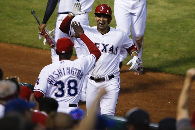 Apr 18, 2014; Arlington, TX, USA; Texas Rangers catcher Robinson Chirinos (61) celebrates with manager Ron Washington (38) after hitting a two run homer against the Chicago White Sox during the third inning of a baseball game at Rangers Ballpark in Arlington. Mandatory Credit: Jim Cowsert-USA TODAY Sports