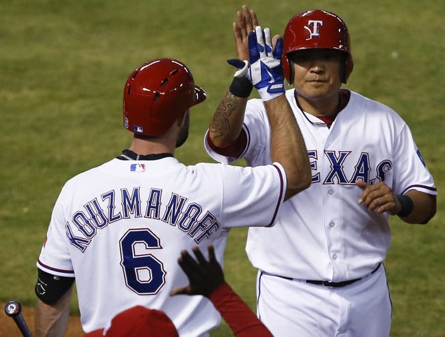 Apr 18, 2014; Arlington, TX, USA; Texas Rangers left fielder Shin-Soo Choo (17) celebrates with third baseman Kevin Kouzmanoff (6) after scoring a run against the Chicago White Sox during the third inning of a baseball game at Rangers Ballpark in Arlington. Mandatory Credit: Jim Cowsert-USA TODAY Sports