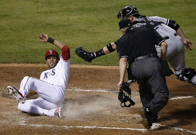 Apr 18, 2014; Arlington, TX, USA; Texas Rangers designated hitter Alex Rios (51) slides home under the tag by Chicago White Sox catcher Tyler Flowers (21) during the third inning of a baseball game at Rangers Ballpark in Arlington. Mandatory Credit: Jim Cowsert-USA TODAY Sports
