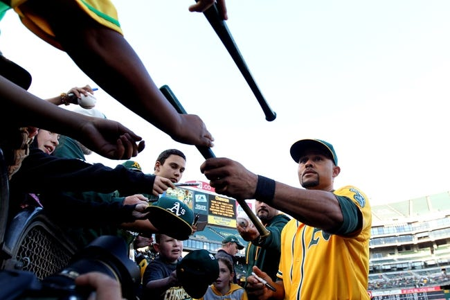 Apr 18, 2014; Oakland, CA, USA; Oakland Athletics center fielder Coco Crisp (4) signs autographs prior to the game with the Houston Astros at O.co Coliseum. Mandatory Credit: Lance Iversen-USA TODAY Sports