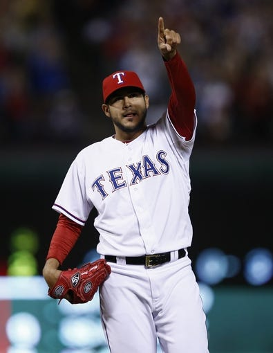 Apr 18, 2014; Arlington, TX, USA; Texas Rangers starting pitcher Martin Perez (33) celebrates after defeating the Chicago White Sox 12-0 at Rangers Ballpark in Arlington. Mandatory Credit: Jim Cowsert-USA TODAY Sports