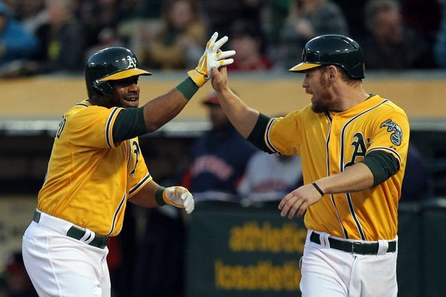 Apr 18, 2014; Oakland, CA, USA; Oakland Athletics Alberto Callaspo (18) is greeted at home plate by first baseman Brandon Moss (37) after hitting a three run home run against the Houston Astros in the first inning of their baseball game at O.co Coliseum. Mandatory Credit: Lance Iversen-USA TODAY Sports