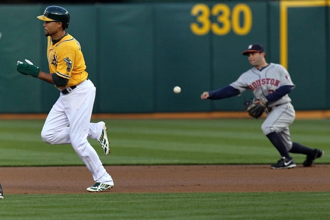 Apr 18, 2014; Oakland, CA, USA; Oakland Athletics center fielder Coco Crisp (4) is thrown out at second base by Houston Astros second baseman Jose Altuve (27) in the first inning of their baseball game at O.co Coliseum. Mandatory Credit: Lance Iversen-USA TODAY Sports