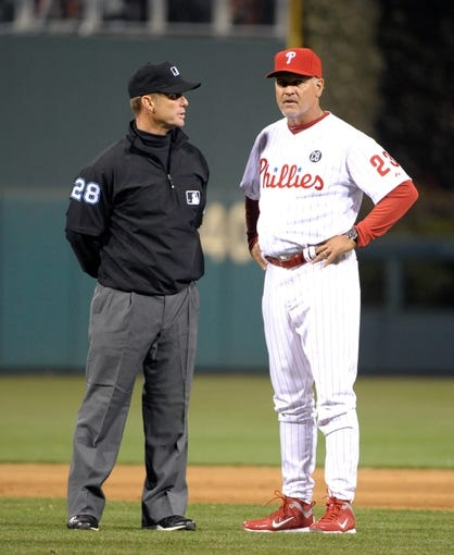Apr 14, 2014; Philadelphia, PA, USA; MLB umpire Jim Wolf (28) and Philadelphia Phillies manager Ryne Sandberg (23) during game against the Atlanta Braves at Citizens Bank Park. The Braves defeated the Phillies, 9-6. Mandatory Credit: Eric Hartline-USA TODAY Sports