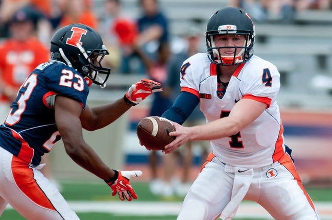 Apr 12, 2014; Champaign, IL, USA;  Illinois Fighting Illini quarterback Reilly O'Toole (4) hands the ball off to Illinois Fighting Illini running back Devin Church (23) during the spring game at Memorial Stadium. Mandatory Credit: Bradley Leeb-USA TODAY Sports
