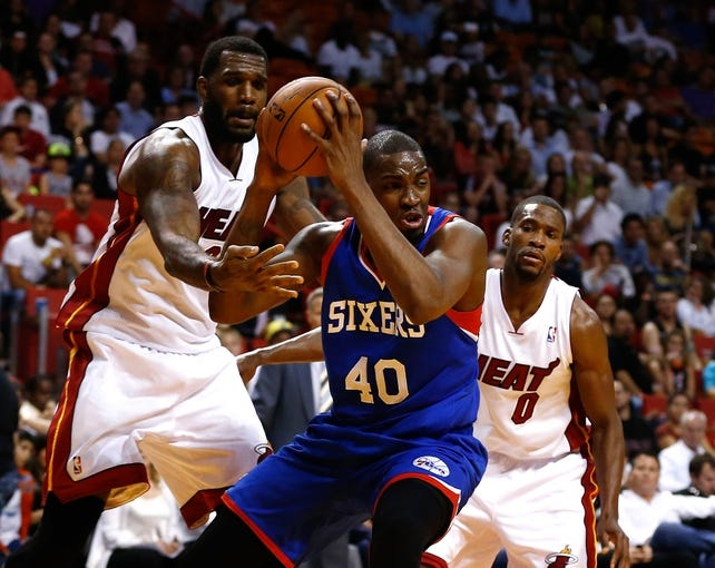 Apr 16, 2014; Miami, FL, USA;  Philadelphia 76ers forward Jarvis Varnado (40) grabs a rebound against Miami Heat center Greg Oden (20) in the second half at American Airlines Arena. The 76ers won 100-87. Mandatory Credit: Robert Mayer-USA TODAY Sports
