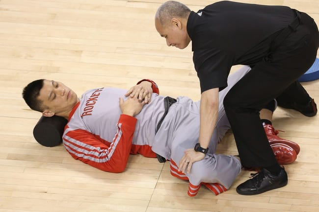 Apr 2, 2014; Toronto, Ontario, CAN; Houston Rockets guard Jeremy Lin (7) warms up with the help of a trainer before the start of their game against the Toronto Raptors at Air Canada Centre. The Raptors beat the Rockets 107-103. Mandatory Credit: Tom Szczerbowski-USA TODAY Sports