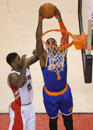 Apr 11, 2014; Toronto, Ontario, CAN; New York Knicks forward Amar'e Stoudemire (1) dunks against Toronto Raptors forward Amir Johnson (15) at Air Canada Centre. The Knicks beat the Raptors 108-100. Mandatory Credit: Tom Szczerbowski-USA TODAY Sports