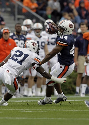 Apr 19, 2014; Auburn, AL, USA;  Auburn Tigers running back Cameron Artis-Payne (44) is tackled by defensive back Mackenro Alexander (21) during the first half of the A-Day spring game at Jordan Hare Stadium. Mandatory Credit: John Reed-USA TODAY Sports