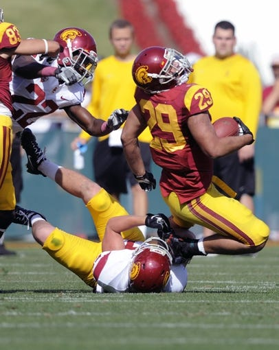 Apr 19, 2014; Los Angeles, CA, USA; Southern California inside linebacker Nick Schlossberg (bottom) tackles Southern California tailback Ty Isaac (29) during the Southern California Spring Game at Los Angeles Memorial Coliseum. Mandatory Credit: Kelvin Kuo-USA TODAY Sports