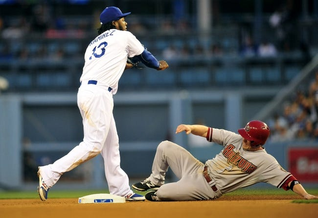 April 19, 2014; Los Angeles, CA, USA; Los Angeles Dodgers shortstop Hanley Ramirez (13) throws to first as Arizona Diamondbacks second baseman Aaron Hill (2) slides into second in the eighth inning at Dodger Stadium. Mandatory Credit: Gary Vasquez-USA TODAY Sports