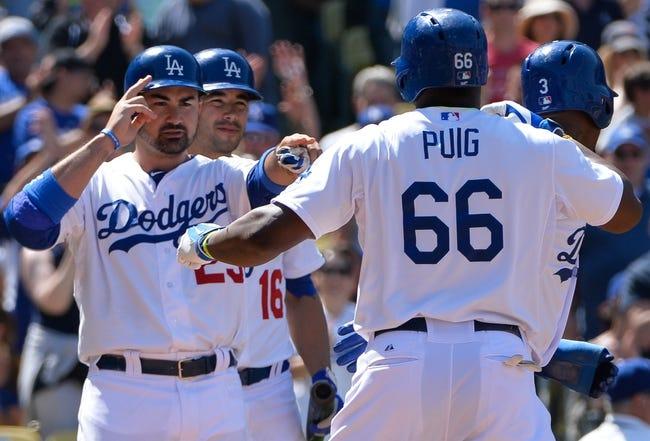 Apr 20, 2014; Los Angeles, CA, USA; Los Angeles Dodgers first baseman Adrian Gonzalez (23) gestures to Dodgers right fielder Yasiel Puig (66) after hitting a three-run homer at Dodger Stadium. Mandatory Credit: Robert Hanashiro-USA TODAY Sports