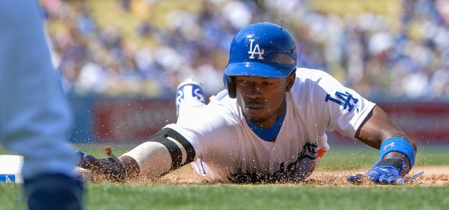 Apr 20, 2014; Los Angeles, CA, USA;  Los Angeles Dodgers second baseman Dee Gordon (9) dives head first back to first base on a  pickoff attempt against Arizona Diamondbacks relief pitcher Josh Collmenter (55) in the sixth inning at Dodger Stadium. Mandatory Credit: Robert Hanashiro-USA TODAY Sports