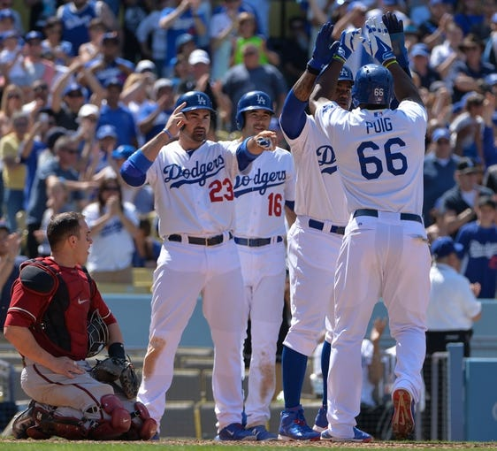 Apr 20, 2014; Los Angeles, CA, USA;  Los Angeles Dodgers right fielder Yasiel Puig (66) celebrates after he crosses home plate after hitting a 3-run homer in the sixth inning against the Arizona Diamondbacks at Dodger Stadium. Mandatory Credit: Robert Hanashiro-USA TODAY Sports