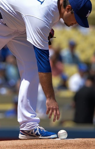 Apr 20, 2014; Los Angeles, CA, USA: Los Angeles Dodgers starting pitcher Josh Beckett (61) reaches for the ball prior to his warmup pitches before the first inning against  the Arizona Diamondbacks at Dodger Stadium. Mandatory Credit: Robert Hanashiro-USA TODAY Sports